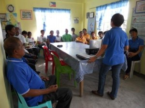 Ms. Marlyn Tejada, ASSRC Presenter, while discussing to a barangay